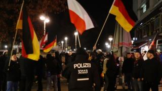 """Far-right protestors demonstrate with flags under the motto """"Close the borders"""" near the Kaiser-Wilhelm-Gedaechtniskirche (Kaiser Wilhelm Memorial Church), two days after an attack at the nearby Christmas market in central Berlin, on December 21, 2016."""
