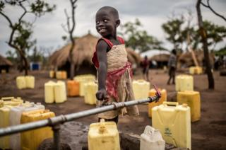 A girl smiles as she fills up her jerrycans with water