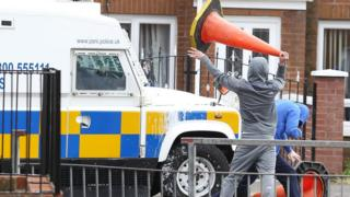 Youth lifts traffic cone next to police vehicle