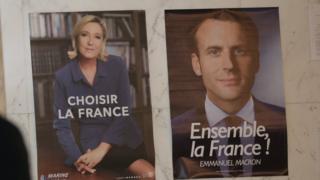 Una mujer camina delante de dos afiches de candidatos politicos