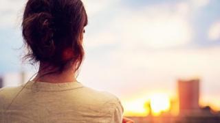 женщина стоит на фоне солнца