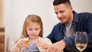 Stock image of father and daughter at table with glass of wine next to man