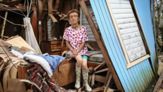 Sonia Torres poses in her destroyed home, three weeks after Hurricane Maria hit, on 11 October 2017 in Aibonito, Puerto Rico