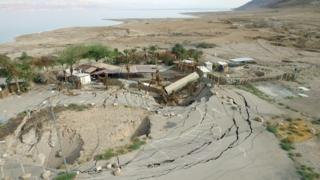 A series of structures that have been swallowed by a sinkhole on the Mineral Beach