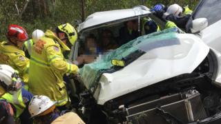 Rescuers work to free the man via the auto wreckage