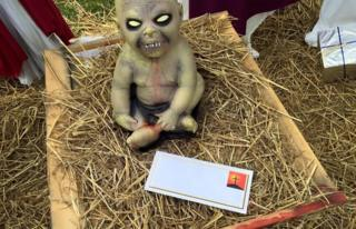 An envelope sits in front of a sculpture of a demon child