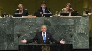 Donald Trump addresses the United Nations with outstretched arms in front of a podium emblazoned with the UN emblem