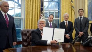 President Donald Trump holds up an executive order