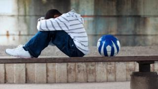 A boy sat with a ball, head in his hands