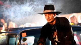Johnny Depp poses on a Cadillac during the Glastonbury Festival