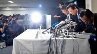 Mitsubishi Motors President Tetsuro Aikawa (second right) arrives at a press conference