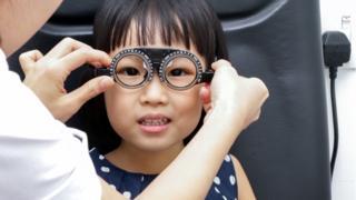 Niña asiática haciéndose un test de visión