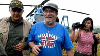 """FARC rebel leader Rodrigo Londono Echeverri (C), better known by his nom de guerre """"Timochenko"""", alights from the helicopter upon his arrival at the Transitional Standardization Zone Mariana Paez, Buena Vista, Mesetas municipality, Colombia on June 26, 2017, for the final act of abandonment of arms and its end as an armed group."""