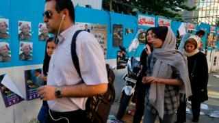 Iranians travel by a wall intoxicated with choosing posters on a travel in a collateral Tehran on 17 May 2017