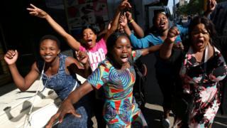Zimbabweans celebrate in the morning sun after President Robert Mugabe resigned in Harare, Zimbabwe, November 22, 2017