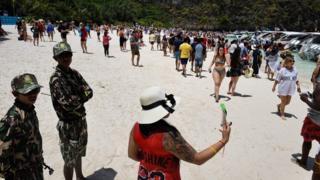 Thai park rangers keeping watch as tourists walk along the Maya Bay beach, Thailand, 9 April 2018