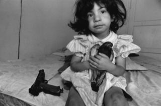 A small girl holds a pigeon whilst a gun lies next to her on the bed, Watts, Los Angeles, 1994.
