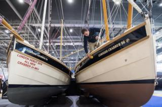 A member of staff polishes a Cornish Crabber sailing boat at the London Boat Show in Docklands, east London.