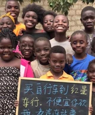 Children pose for a group picture behind a black board.
