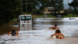 Residents in Billinudgel, NSW, used surf boards to paddle down the street.