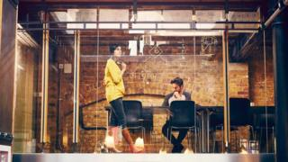 Unas personas trabajando en una oficina con pared de vidrio