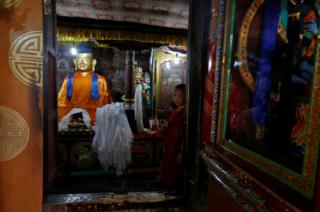 A young Buddhist monk stands inside Thiksey monastery, Ladakh, India.