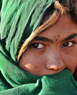 An Afghan girl from a family which returned from Iran covers her face as she stands in front of her tent on the outskirts of Kabul, February 2008