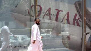 A picture taken on June 5, 2017 shows a man walking past the Qatar Airways branch in the Saudi capital Riyadh, after it had suspended all flights to Saudi Arabia following a severing of relations between major gulf states and gas-rich Qatar