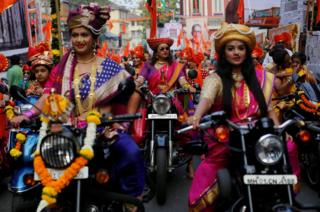 Women dressed in traditional costumes ride motorbikes.