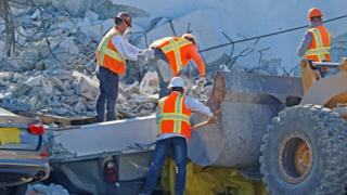 Workers remove debris from a collapsed pedestrian bridge at Florida International University in Miami, Florida on 16 March 2018.