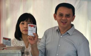Incumbent Jakarta governor Basuki Tjahaja Purnama (R) and his wife Veronica (C) show ballot papers at a polling station during the final-round of the Jakarta governor election in Jakarta on 19 April 2017.