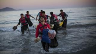 Migrants leaving a dinghy and walking on to a beach in Kos, Greece