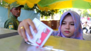 An Indonesian woman casts her vote in local elections at a polling station in Banda Aceh