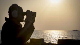 Soldado a bordo del buque destructor estadounidense USS Stethem mirando a la distancia con binoculares
