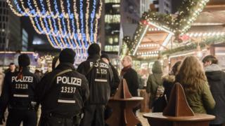 Police officers walk at the christmas market near the Kaiser-Wilhelm-Gedaechtniskirche (Kaiser Wilhelm Memorial Church) in Berlin on December 22, 2016.
