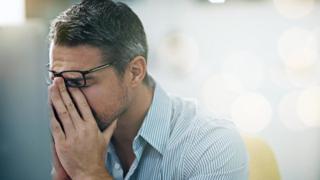 رجل مجهد أمام شاشة كمبيوتر