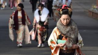 Twenty-year-old women wearing kimonos leave after attending a 'Coming-of-Age Day' celebration