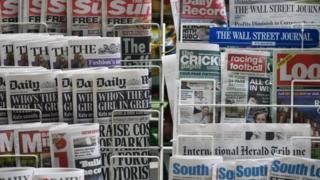 Newspapers displayed on a stand