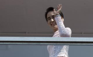 Myanmar opposition leader Aung San Suu Kyi waves to a small crowd and the media after delivering a speech from the balcony of the National League of Democracy (NLD) headquarters in Yangon on 9 November 2015.