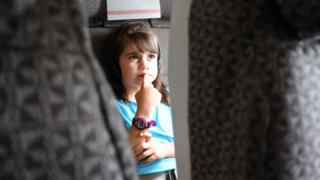 A girl watching a film on a plane