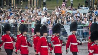 السواح يقفون أمام قصر باكينغهام ويشاهدون تبديل الحرس الملكي