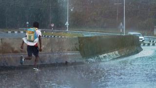 Un élève surpris par une forte pluie court sur une route au Kenya (illustration)