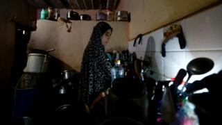 A Palestinian woman cleans the dishes using an LED lamp during a blackout in Gaza City on 20 June 2017