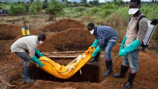 Volunteers in protective suit burry the body of a person who died from Ebola in Waterloo, some 30 kilometers southeast of Freetown, on October 7, 2014.