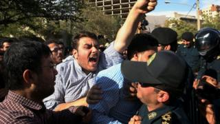 An Iranian protester chants slogans while police officers prevent him from approaching to the Saudi Arabian Embassy in Tehran, Iran, Sunday, Sept. 27, 2015,
