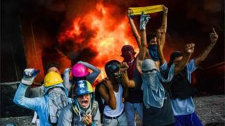 A masked group of youths take part in an attack on the administration headquarters of the Supreme Court of Justice as part of protests against President Nicolas Maduro in Caracas, on June 12, 2017.
