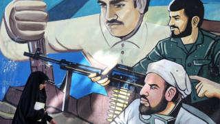 Woman wearing veil and sunglasses walks past mural depicting three men with guns