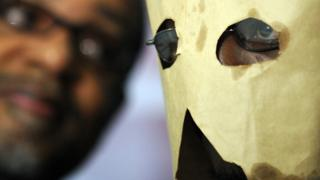 Moses (R), a gay Ugandan man seeking asylum in the United States, hides his face with a makeshift hood as he attends a press conference in Washington, DC - 2010