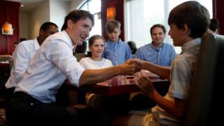 Pm Trudeau shaking a kids hand.