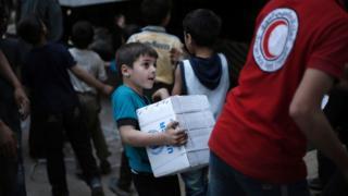 Elinde yardım paketi taşıyan Suriyeli bir çocuk